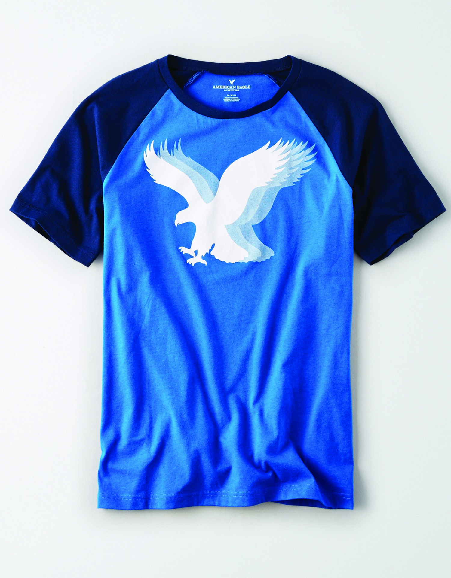 AE - M - Apparel - OPP SS RAGLAN TEE - Cobalt Blue Body - Navy Blue sleeves and collar - white and light blue layered eagle graphic on chest JP *Tracked